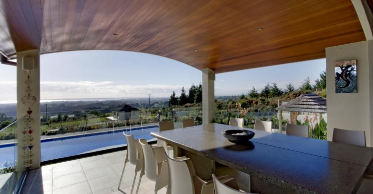 Alfresco dining overlooking the pool and landscaped gardens